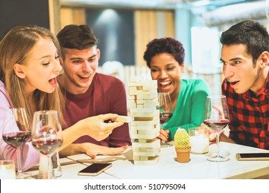 Group of young friends having fun playing wood board game in pub wine shop - Multiracial cheerful people smiling and enjoying time together indoor - Friendship concept - Focus on left girl eye