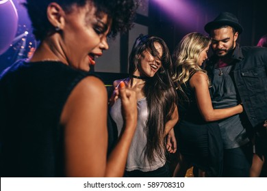 Group of young friends having fun together at the nightclub. Men and women dancing at disco.