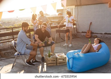 Group of young friends having fun at rooftop party, making barbecue, drinking beer and enjoying hot summer days. Focus on the man in black T-shirt