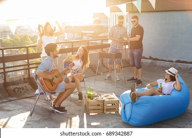 Group of young friends having fun at rooftop party, making barbecue, drinking beer, playing the guitar and enjoying hot summer days. Focus on the girl sitting on the chair