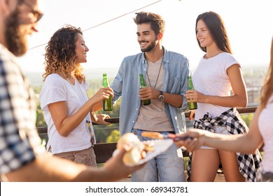 Group of young friends having fun at rooftop party, drinking beer, eating barbecue and enjoying hot summer days. Focus on the couple on the right