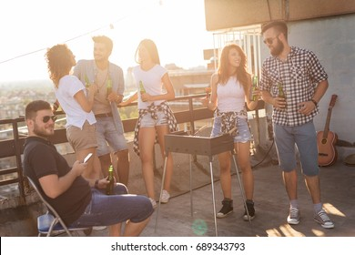 Group of young friends having fun at rooftop party, making barbecue, drinking beer and enjoying hot summer days. Focus on the couple next to the barbecue