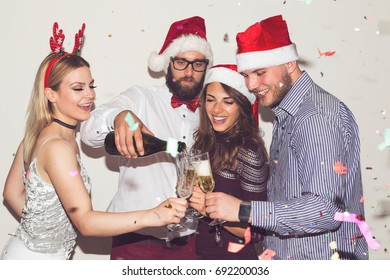 Group of young friends having fun at New Year's Eve party, pouring champagne into glasses and making a midnight toast