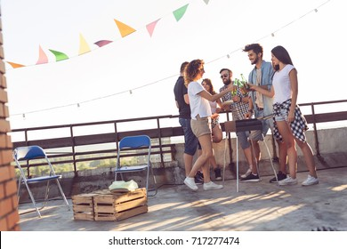 Group of young friends having fun at rooftop party, making barbecue, drinking beer and enjoying hot summer days. Focus on the couple in the middle