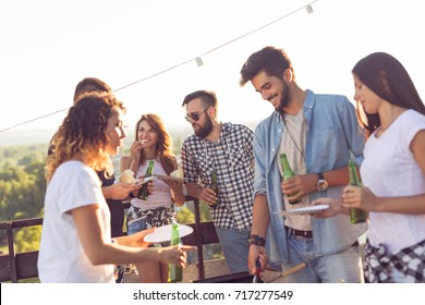 Group of young friends having fun at rooftop party, making barbecue, drinking beer and enjoying hot summer days. Focus on the girl in the middle