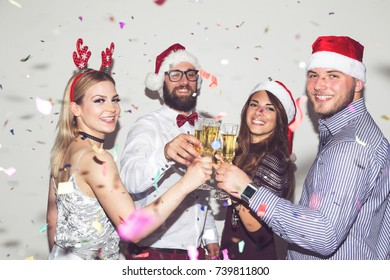 Group of young friends having fun at New Year's Eve party, making a midnight toast with glasses of champagne