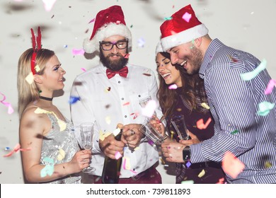 Group of young friends having fun at New Year's Eve party, opening a bottle of champagne and making a midnight toast