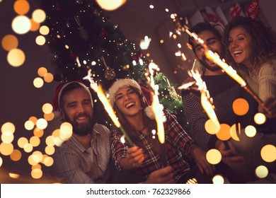 Group of young friends having fun at a New Year's celebration, holding sparklers at a midnight countdown.