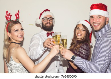 Group of young friends having fun at New Year's Eve party, making a midnight toast with glasses of champagne. Focus on the couple in the middle
