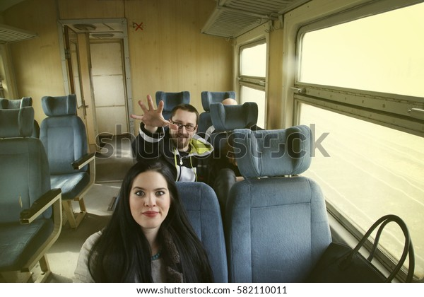 Group of young friends having fun interaction and talking in train with blue seats