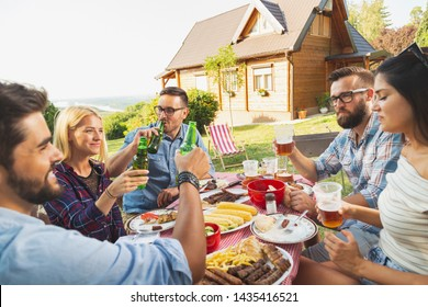 Group of young friends having an outdoor barbecue lunch, making a toast while sitting at the table, drinking beer