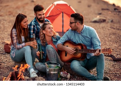 Group of young friends having picnic at night,they are having fun.
