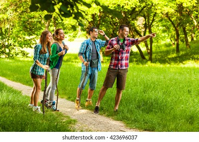 Group of young friends hiking trough forest on beautiful summer day