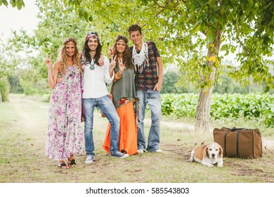 Group of young friends in hippie style with a dog standing in nature and gesturing peace sign