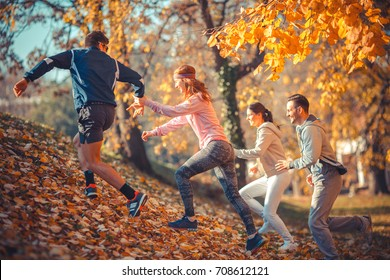 Group of young friends jogging at the park.Autumn season.They run up the hill and making fun.