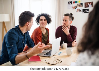 A group of young friends with laptop indoors, house sharing concept.