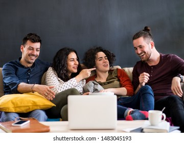 A group of young friends with laptop sitting on sofa indoors, watching film.