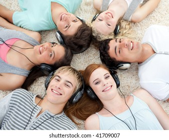 Group of young friends listening to music on the floor