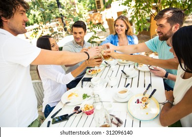 Group of a young friends making toast around table at dinner party in outdoor restaurant