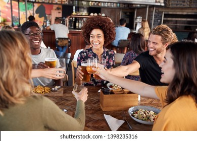 Group Of Young Friends Meeting For Drinks And Food Making A Toast In Restaurant