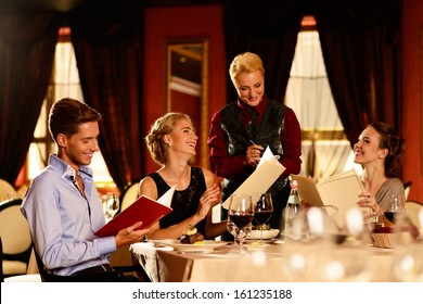 Group of young friends with menus choosing in a luxury restaurant