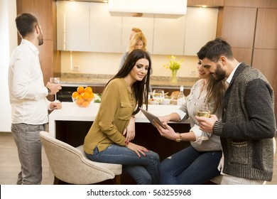 Group of young friends are in modern kitchen, talking to each other while preparing food