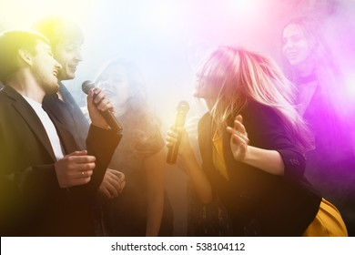 Group of young friends on party singing at karaoke club. Friendship and happiness