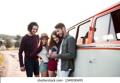A group of young friends on a roadtrip through countryside, using smartphone.