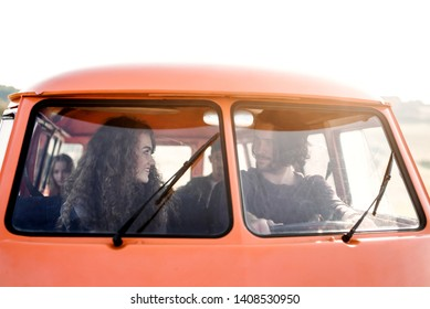 A group of young friends on a roadtrip through countryside, sitting in a minivan.