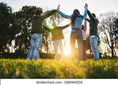 Group of young friends at park at sunset in circle with hands upwards - Teens in a moment of unity, fraternity, strength and team building