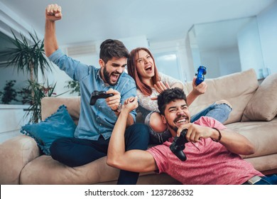 Group of young friends play video games together at home.