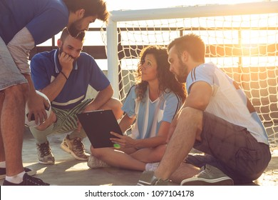 Group of young friends playing a football match on a building rooftop, on a time out, discussing the game strategy. Focus on the girl