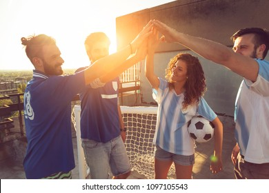 Group of young friends playing football on a building rooftop, greeting each other with high five before the game. Focus on the girl