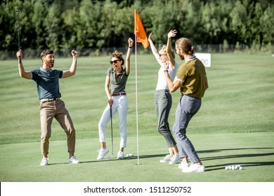 Group of a young friends playing golf, scoring the ball with putter into the hole on the beautiful course during a sunny day