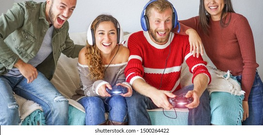 Group of young friends playing video games streaming online - Happy people having fun with new console trend technology - Tech, youth concept, winter holidays, - Focus on right couple