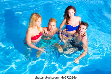 A group of young friends relaxing together in a swimming pool.