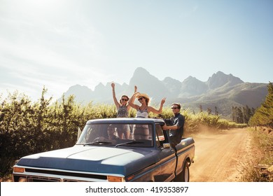 Group of young friends riding in pickup truck having fun on summer day