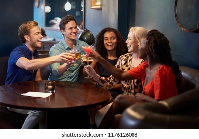 Group Of Young Friends Sitting Around Table And Making A Toast In Bar On Night Out