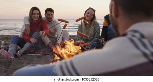 Group of young friends sitting by the fire late at night, grilling sausages and drinking beer, talking and having fun