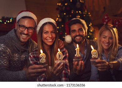 Group of young friends sitting next to a Christmas tree, wearing Santa's hats, holding cupcakes with 2019 candles on them. Focus on the girl on the left