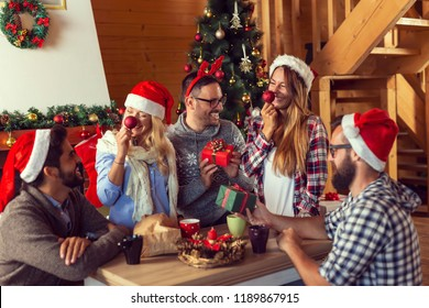 Group of young friends sitting next to a nicely decorated Christmas tree, exchanging Christmas presents and having fun. Focus on the couple in the middle