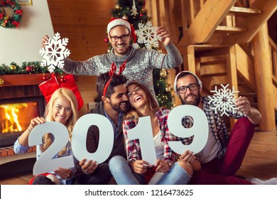 Group of young friends sitting on the floor next to a fireplace and nicely decorated Christmas tree, wearing Santa's hats and holding a cardboard snowflakes and numbers 2019