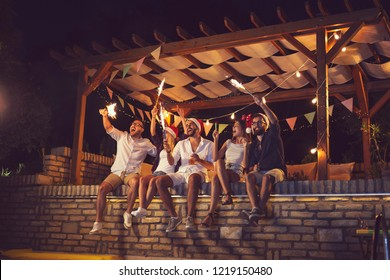 Group of young friends sitting on a poolside brick wall, having fun on a New Year's Eve, dancing, drinking beer and waving with sparklers at midnight