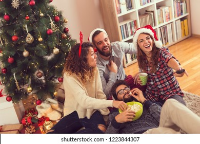 Group of young friends sitting on the floor next to a Christmas tree, eating popcorn and watching a Christmas movie