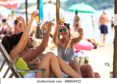 Group of young friends sitting on  sunbeds at the riverside beach, relaxing and drinking beer.Summer beach party.