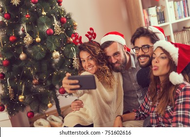 Group of young friends sitting on the floor next to a nicely decorated Christmas tree, wearing Santa's hats and taking a selfie. Focus on the couple on the left