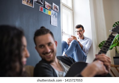 A group of young friends with smartphone indoors, house sharing concept.