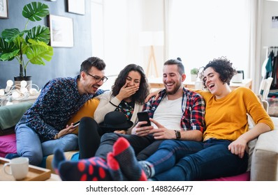 A group of young friends with smartphone sitting on sofa indoors, house sharing concept.