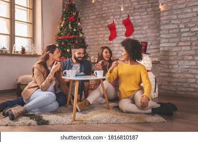 Group of young friends spending Christmas day at home together, drinking coffee, eating Christmas cookies and having fun