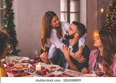 Group of young friends spending Christmas day togehter at home, having fun over Christmas dinner; couple in love having Christmas dinner for friends at home